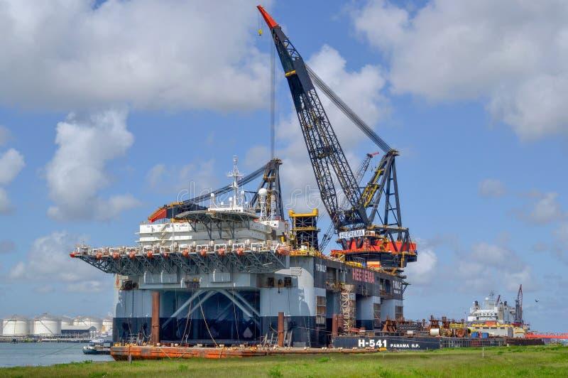 Det Thialf kranskeppet, en stor deepwater konstruktionsskyttel från Heerema förtöjde på porten royaltyfri fotografi