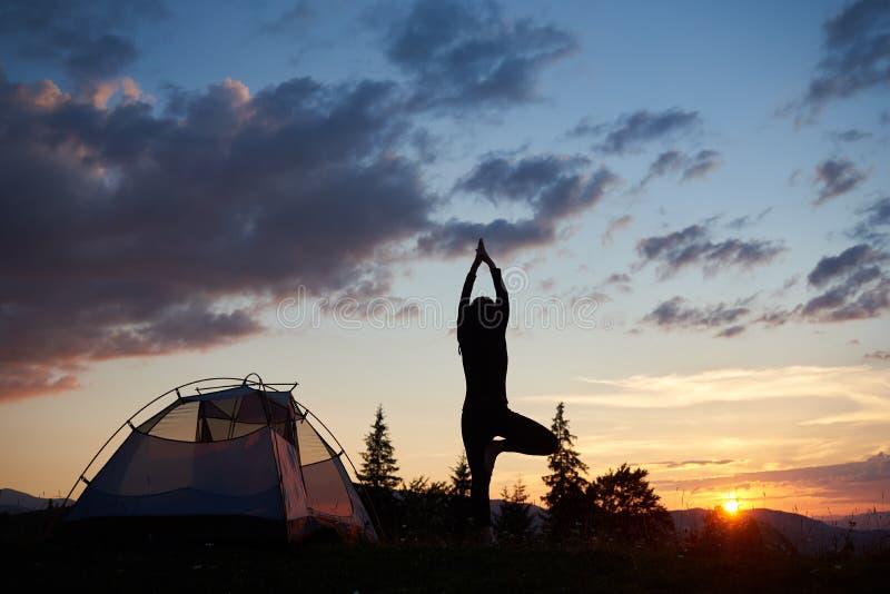 Det tillbaka anseendet för ung kvinna för siktskontur på benet i yogaträd poserar överst av kullen nära tältet arkivbild