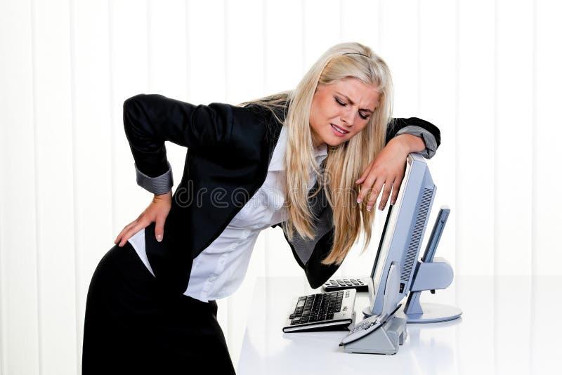 det tillbaka kontoret smärtar kvinnan arkivfoton