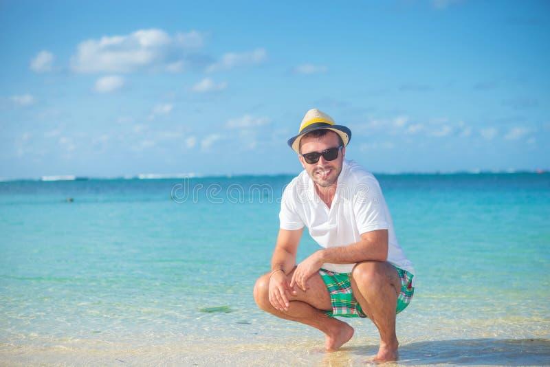 Det tillfälliga mananseendet huka sig ned på en tropisk strand royaltyfria bilder