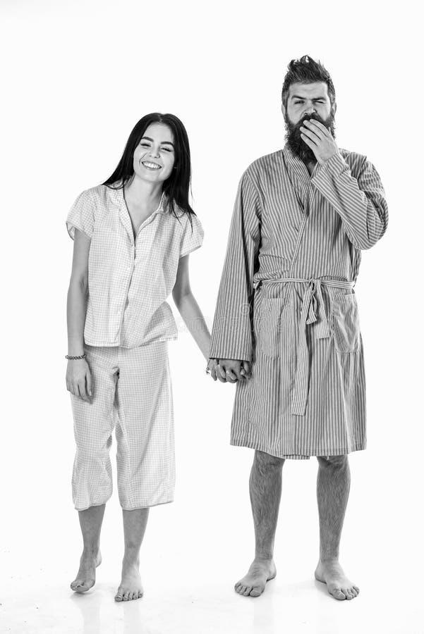 Det tillfredsställda barnet kopplar ihop förälskat kela försiktigt i pyjamas hemma Förälskade hållhänder för par som isoleras på  royaltyfri fotografi