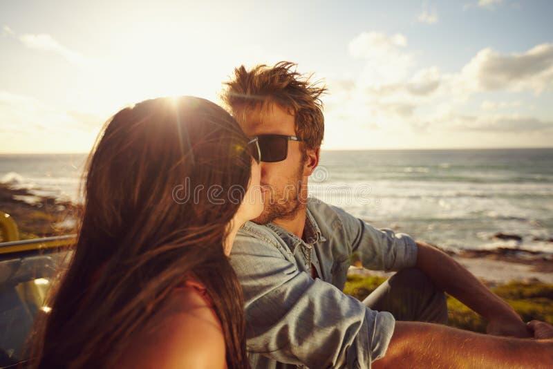 Det tillgivna barnet kopplar ihop att kyssa på stranden arkivfoton
