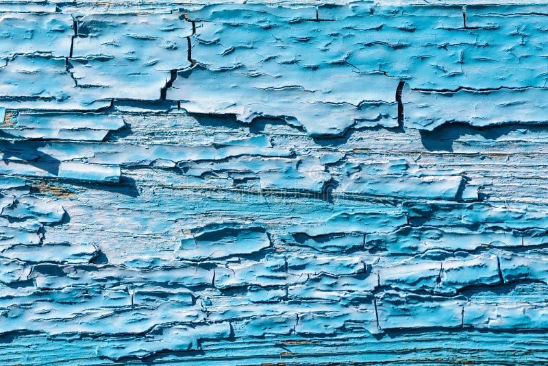 Det tjocka lagret av knäckte blått målar på brädet arkivfoton