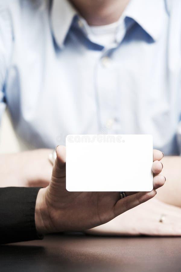 Det tomma affärskortet, vit, rymmer med hennes fingrar och hand royaltyfria bilder