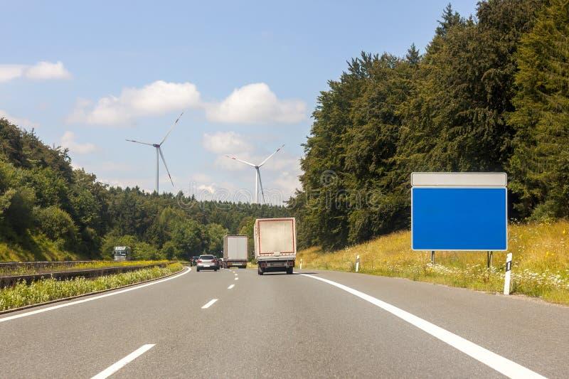 Det tomma blåa teckenbrädet på vägrenen på motorväg i sommar landar arkivfoton