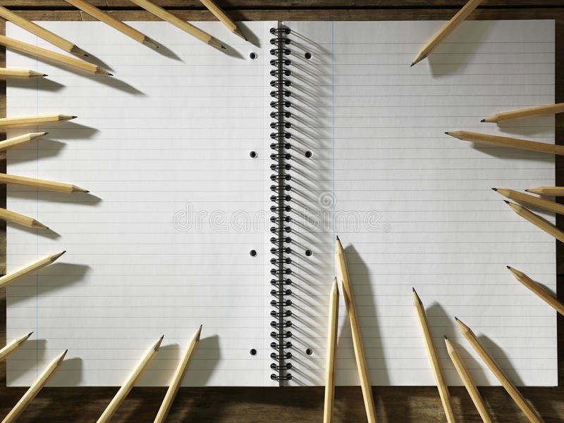 Det tomma blocket av papper och cirkeln av vässar blyertspennor fotografering för bildbyråer