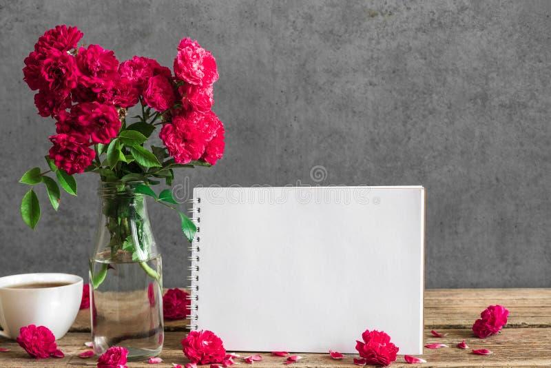 Det tomma hälsa kortet och steg blommor med kopp te på den lantliga trätabellen Åtlöje upp gifta sig för trappa för stående för b royaltyfri foto