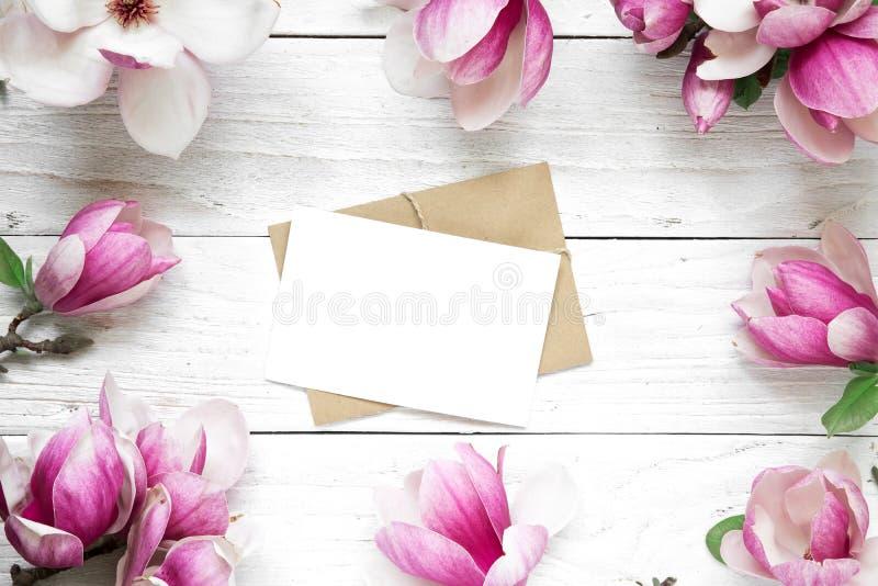 Det tomma hälsningkortet eller bröllopinbjudan i ramen som göras av rosa magnolia, blommar fotografering för bildbyråer