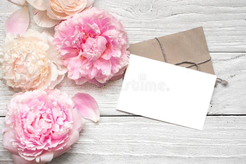 Det tomma hälsningkortet eller bröllopinbjudan med den rosa och krämiga pionen blommar över den vita trätabellen arkivbilder