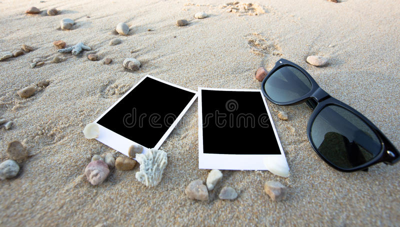 Det tomma polaroidfotoet skrivar ut och solexponeringsglas på en havssand royaltyfri bild