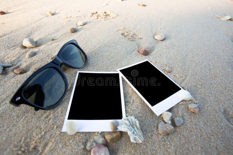 Det tomma polaroidfotoet skrivar ut och solexponeringsglas på en havssand fotografering för bildbyråer