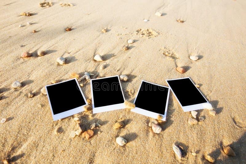 Det tomma polaroidfotoet skrivar ut på en havssand med skal Solig summ royaltyfria bilder