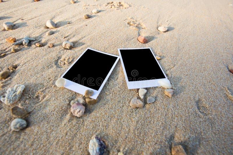 Det tomma polaroidfotoet skrivar ut på en havssand med skal Solig summ arkivfoton
