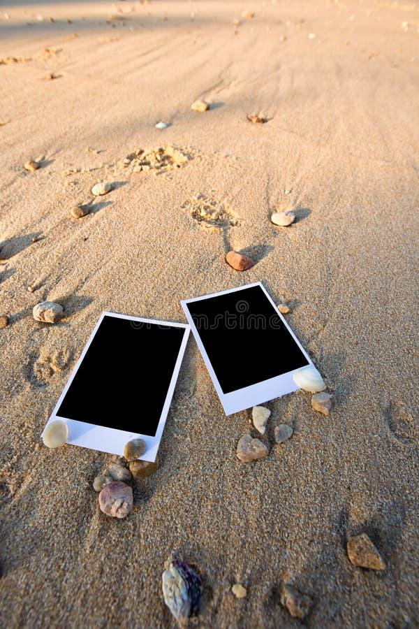 Det tomma polaroidfotoet skrivar ut på en havssand med skal Solig summ royaltyfri foto