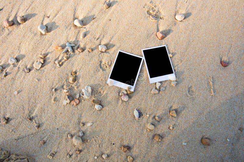 Det tomma polaroidfotoet skrivar ut på en havssand med skal Solig summ arkivbilder