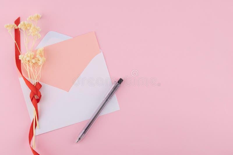 Det tomma rosa kortet i vit packar och svärtar pennan in arkivbilder