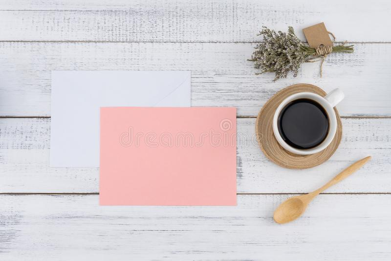 Det tomma rosa kortet och vit packar in med en kopp kaffe royaltyfria bilder