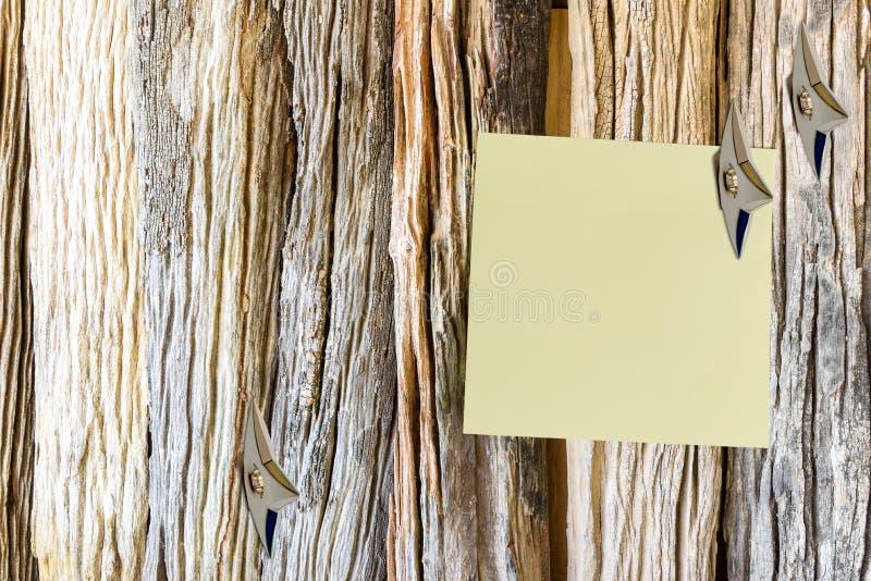 Det tomma stycket av papper fäste på en gammal trävägg royaltyfri foto