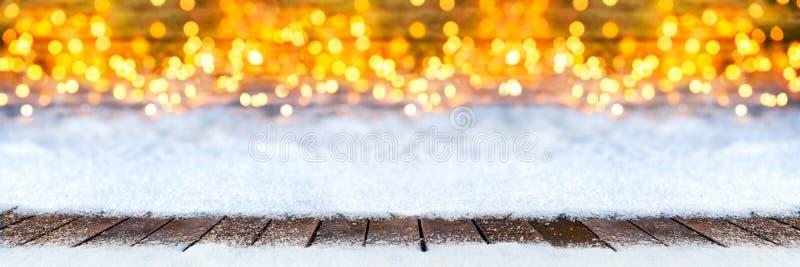 Det tomma träplankagolvet på jul snöar varma lodisar för ljusbokeh royaltyfria bilder