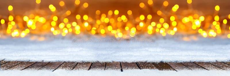 Det tomma träplankagolvet på jul snöar varma lodisar för ljusbokeh arkivbild