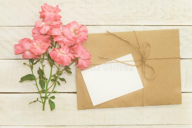 Det tomma vita hälsningkortet med rosa färgrosen blommar buketten och env arkivbilder
