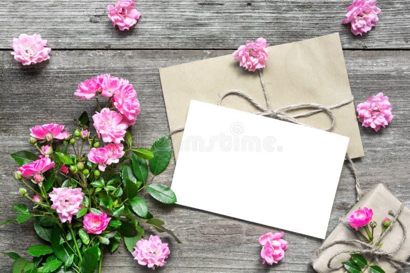 Det tomma vita hälsningkortet med rosa färgrosen blommar buketten och kuvertet med blommaknoppar och gåvaasken royaltyfri foto