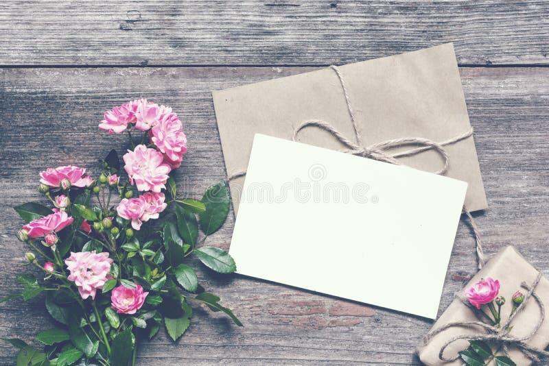 Det tomma vita hälsningkortet med rosa färgrosen blommar buketten och kuvertet med gåvaasken arkivbilder