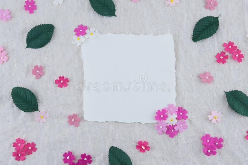 Det tomma vita kortet som dekoreras med rosa färger, tonar pappers- blommor arkivbild