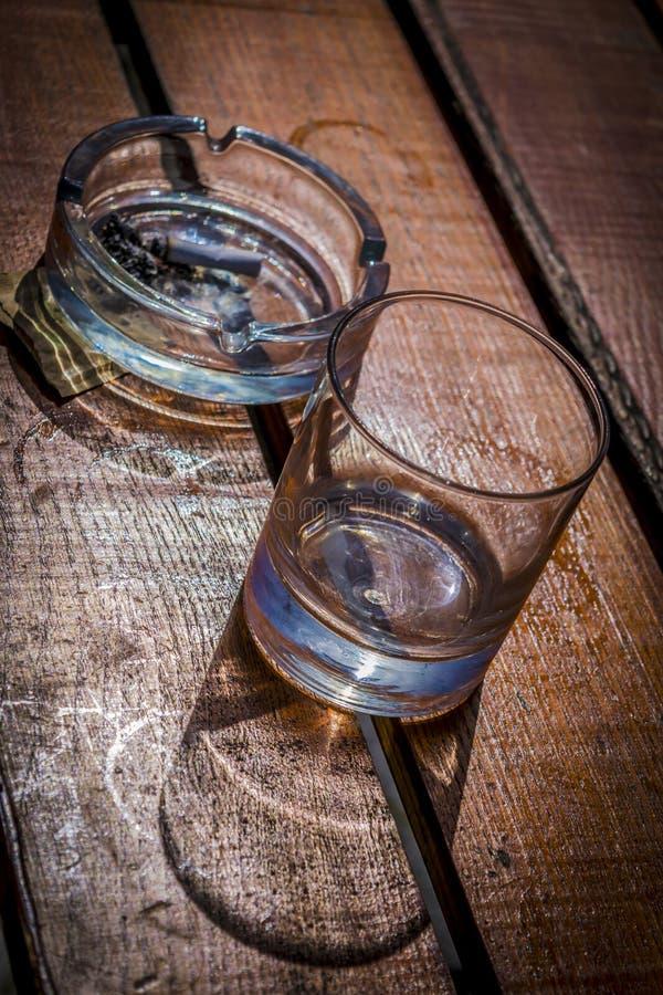 Det tomma whiskyexponeringsglas och askfatet med cigaretten klibbar på trätabellen royaltyfri foto