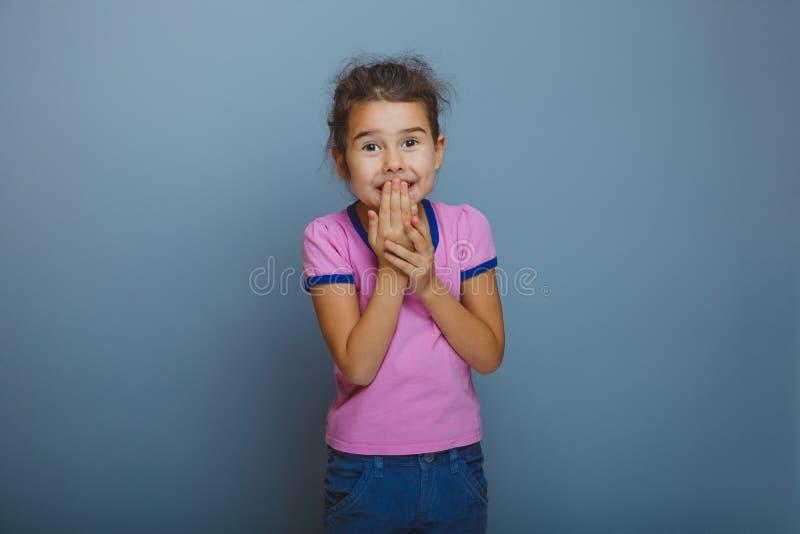 Det tonåriga flickabarnet är den lyckliga överraskningen på grå färger arkivbild
