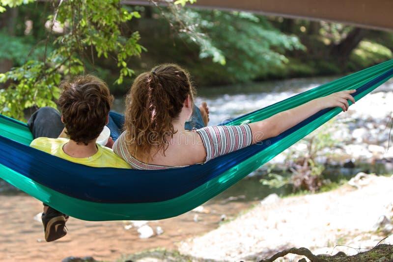 Det tonårs- paret sitter i hängmattan som ser Serene River royaltyfria bilder