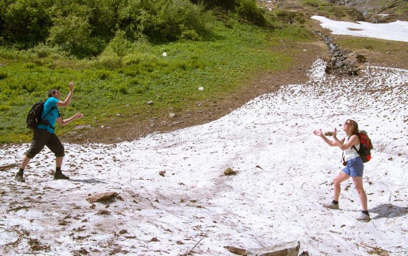 Det tonade bildgifta paret med ryggsäckar och i att spela för kortslutningar, kastar snöboll royaltyfri bild
