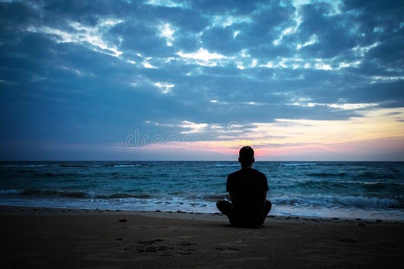 Det tonade fotoet av den ensamma mannen sitter på bänken på solnedgångbakgrund royaltyfri bild