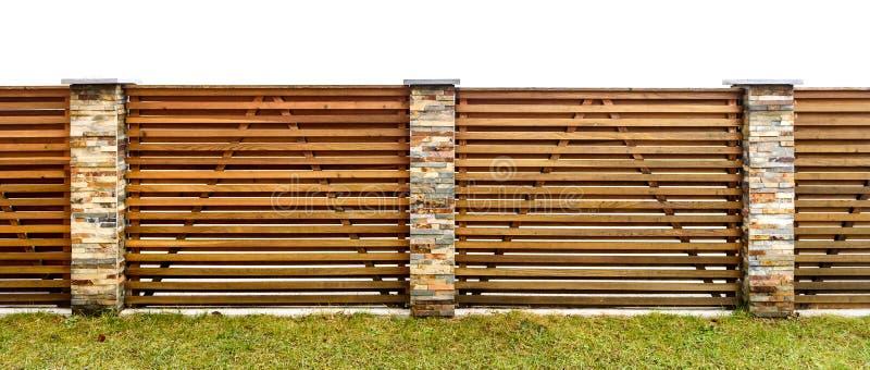 Det träträdgårds- staketet med stenen stenlade pelare som bevakar privat pr arkivbilder
