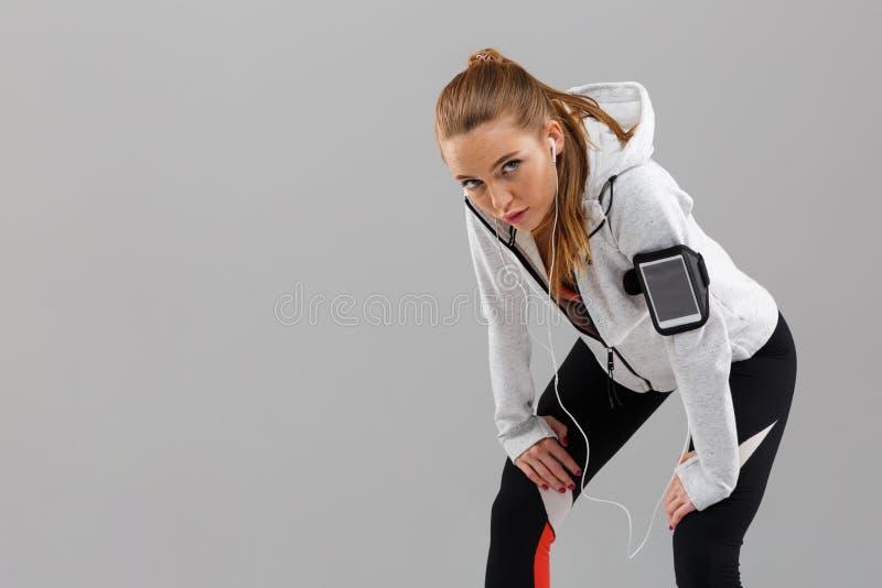 Det trötta anseendet för sportkvinnalöpare isolerade lyssnande musik vid hörlurar royaltyfri fotografi