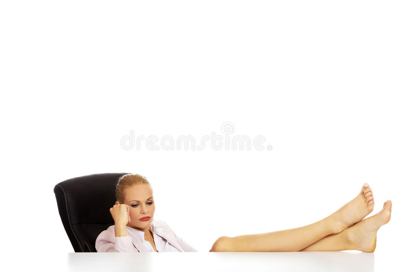 Det trötta unga innehavet för affärskvinnan lägger benen på ryggen på skrivbordet arkivbild