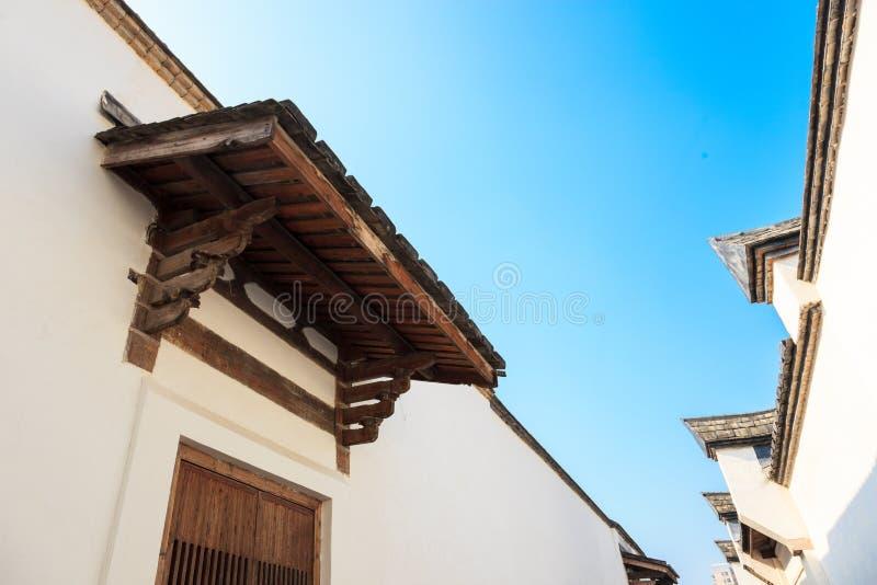 Det traditionella kinesiska taket och väggen mot en blå himmel royaltyfri bild