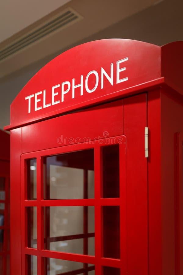 Det traditionella röda telefonbåset står inomhus som ett symbol av London och UK royaltyfria bilder