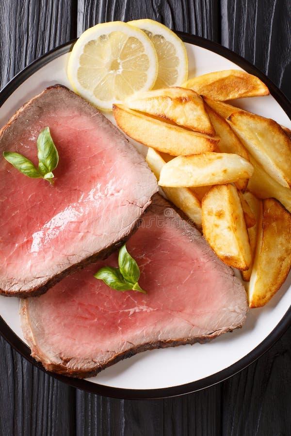 Det traditionella receptet av nötköttbiff tjänas som med grillade potatisar royaltyfri fotografi