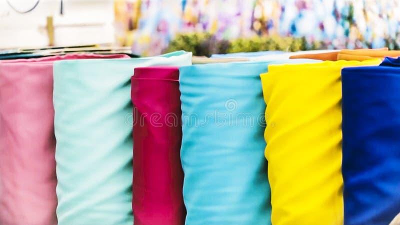 Det traditionella tyglagret med buntar av färgrika textiler, tyg rullar på stånd - bakgrund för textilbransch med suddigt royaltyfri bild