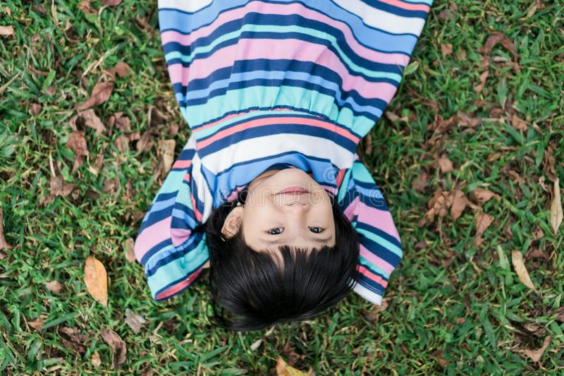Det trevliga leendet av lilla flickan, när koppla av, ligger ner royaltyfri bild