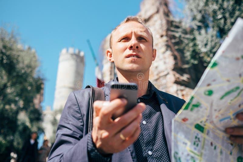 Det turist- manförsöket navigerar sig med översikten och smartphonen i unkn arkivfoton