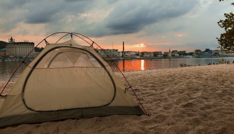 Det turist- tältet möter solnedgången på stadsstranden av den Dnipro floden i Kiev, Ukraina royaltyfria bilder