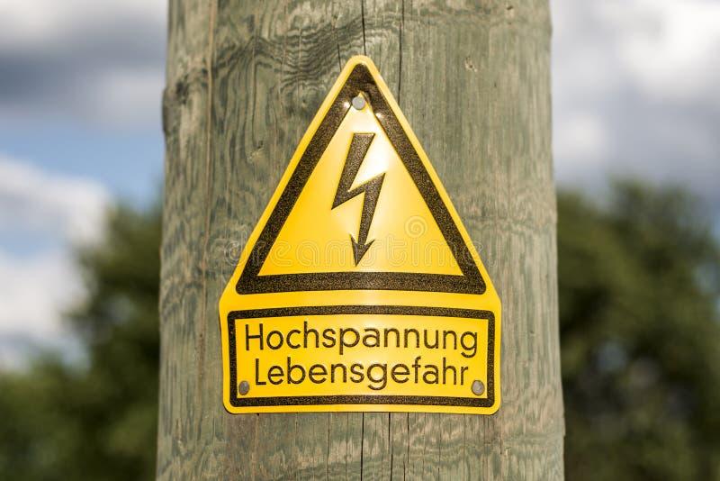 Det tyska höga spänningstecknet monterade på träpol med gröna träd i bakgrund fotografering för bildbyråer