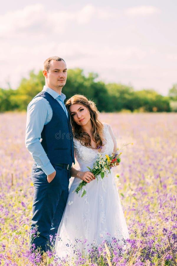 Det underbara unga paret, brud lägger på bröstkorgen av hennes älskade brudgum, ställning i ett fält med purpurfärgade blommor, f royaltyfria bilder