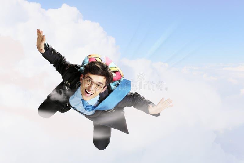 Det unga affärsmanflyget med hoppa fallskärm på baksida royaltyfria bilder