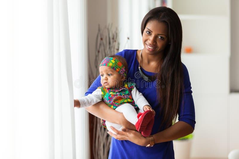 Det unga afrikansk amerikanmoderinnehavet med hennes behandla som ett barn flickan royaltyfria foton