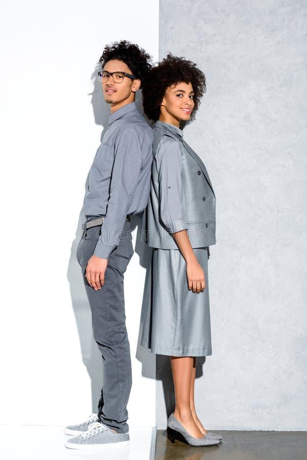 Det unga afrikanska amercian le paret i grå färger passar stående tillbaka för att dra tillbaka och se kameran på grå färger och  arkivfoton