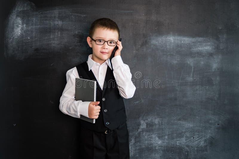 Det unga anseendet för pojke` s med telefonen och anteckningsboken i hans händer near svart tavla Ung affärsman Idérikt designbeg royaltyfri bild