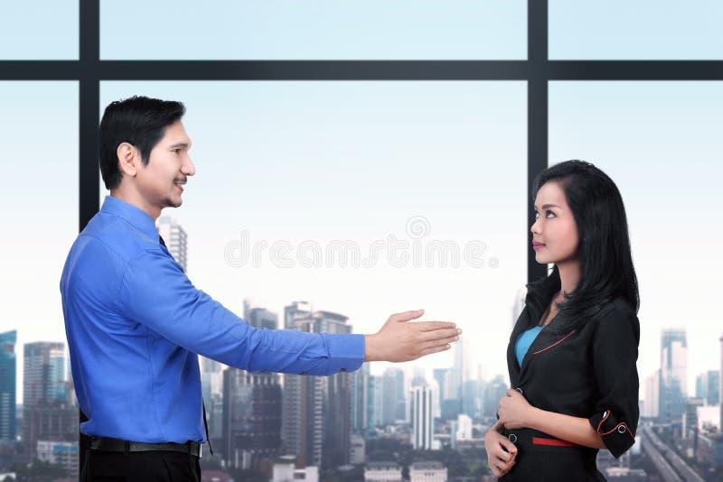 Det unga asiatiska affärsmanerbjudandet skakar händer till affärskvinnan för D royaltyfri bild